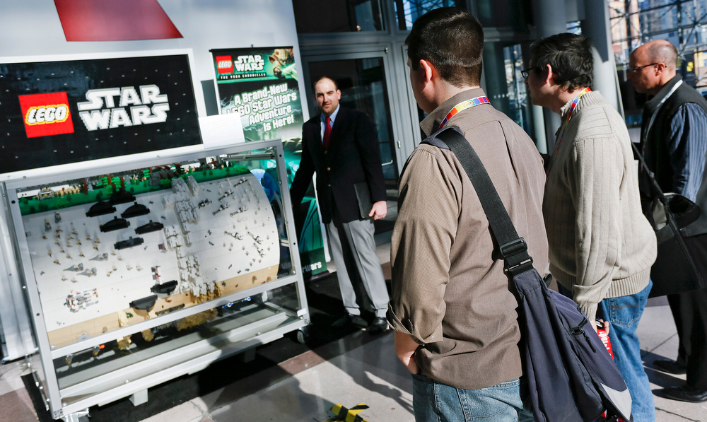 . Peter Day of LEGO Systems shows attendees of the American International Toy Fair a LEGO Star Wars hand-crank barrel organ that plays the iconic film sagaís theme song as the custom-built LEGO landscape spins around and hits the keys of the organ on Sunday, Feb 10, 2012, in New York City. (Brian Ach/AP Images for LEGO Systems, Inc.)