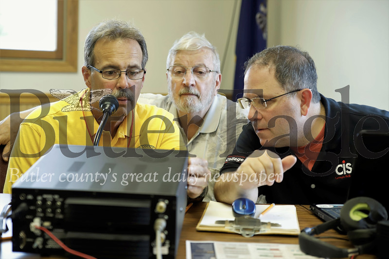 Tom McCracken(center) looks on as Denny Stokes (left) and Tom Grasso attempt to make radio contact with another ham radio operator. Seb Foltz/Butler Eagle