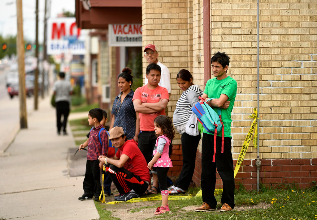 . DENVER, CO - MAY 9:  Neighborhood residents watch as Denver police officers investigate the scene of an officer involved shooting at Colfax ave between Wabash and Verbena streets on May 9, 2016 in Denver, Colorado. One person was transported to an area hospital in critical condition. (Photo by Helen H. Richardson/The Denver Post)