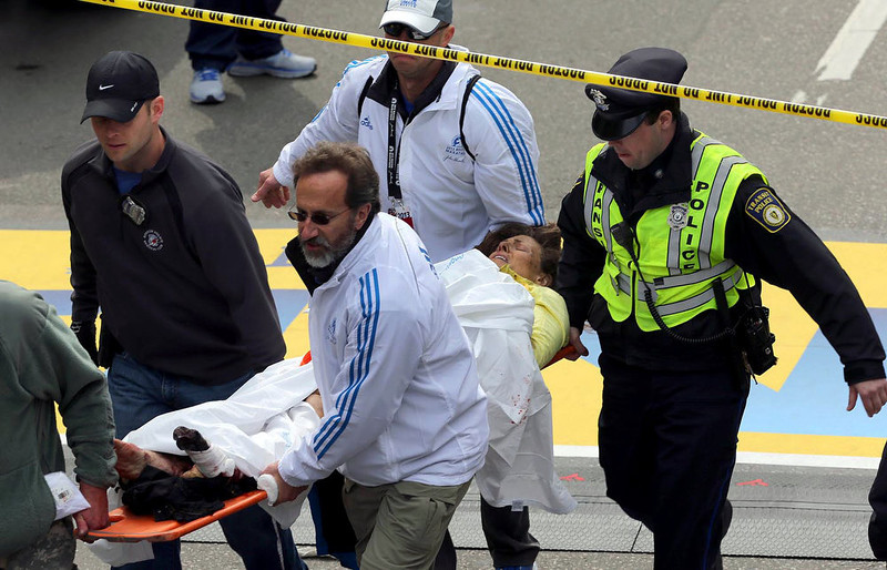 . Medical workers aid injured people at the finish line of the 2013 Boston Marathon following an explosion in Boston, Monday, April 15, 2013. Two explosions shattered the euphoria of the Boston Marathon finish line on Monday, sending authorities out on the course to carry off the injured while the stragglers were rerouted away from the smoking site of the blasts. (AP Photo/The Boston Globe, David L Ryan)