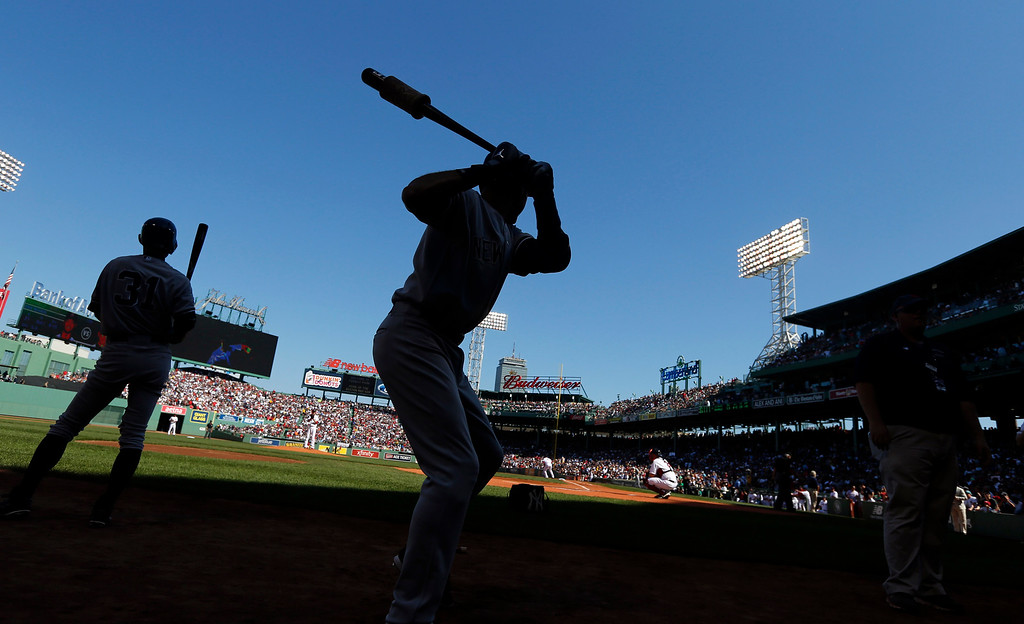 . New York Yankees designated hitter Derek Jeter, center, warms up in the on-deck circle for his at-bat in the first inning of a baseball game against the Boston Red Sox, Sunday, Sept. 28, 2014, at Fenway Park in Boston. (AP Photo/Elise Amendola)