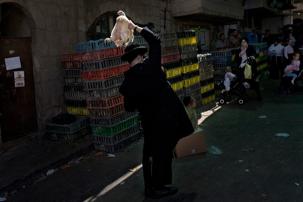 . An ultra-Orthodox Jewish man holds a chicken, later to be slaughtered as part of the Kaparot ritual, in which it is believed that one transfers one\'s sins from the past year into the chicken, in Jerusalem\'s religious Mea Shearim neighborhood, Wednesday, Sept. 11, 2013. (AP Photo/(Bernat Armangue)