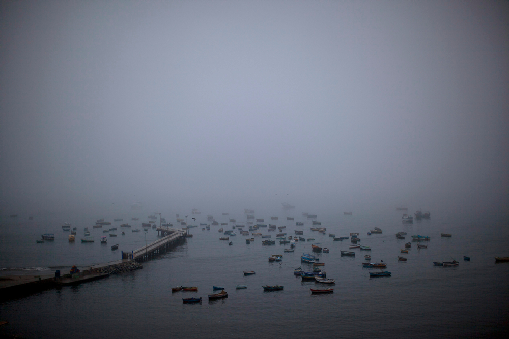 . Morning fog lifts at the Chorrillo dock in the Pacific Ocean, revealing small scale fishing boats in Lima, Peru, Wednesday, April 2, 2014. Chilean authorities discovered surprisingly light damage Wednesday from a magnitude-8.2 quake that struck in the Pacific Ocean, Tuesday evening, near the mining port of Iquique, about 87 miles from the Peruvian border. Tsunami warnings issued for Chile, Peru and Ecuador have been lifted. Six deaths have been reported. (AP Photo/Rodrigo Abd)