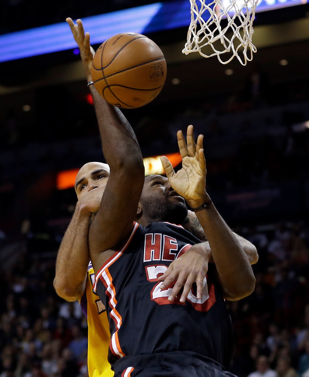 . Miami Heat center Greg Oden (20) is fouled by Los Angeles Lakers center Robert Sacre (50) during the first quarter of an NBA basketball game in Miami, Thursday, Jan. 23, 2014. (AP Photo/Alan Diaz)