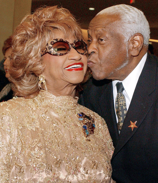 . HOLLYWOOD, UNITED STATES:  Cuban-born singer Celia Cruz (L) is kissed by her husband Pedro Knight as they arrive at the 2002 Latin Recording Academy (LARAS) Person of the Year Award tribute gala to Vicente Fernandez, in Hollywood, CA, 17 September 2002.   (LUCY NICHOLSON/AFP/Getty Images)