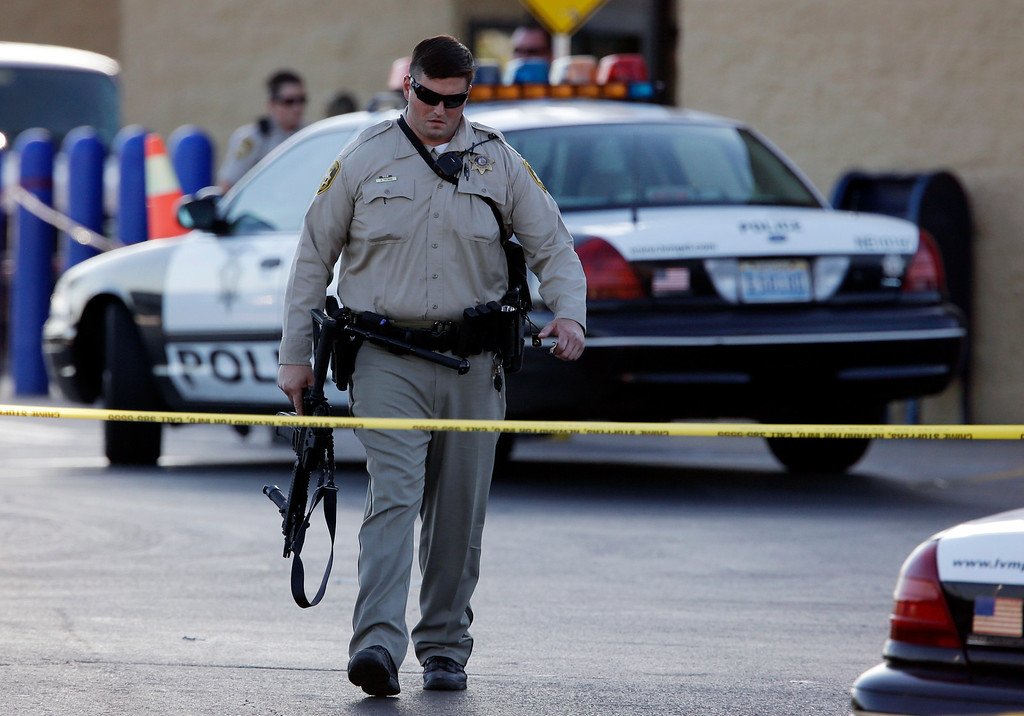 . A Las Vegas police officer walks away from the scene of a shooting near a Wal-Mart, Sunday, June 8, 2014, in Las Vegas.  (AP Photo/John Locher)