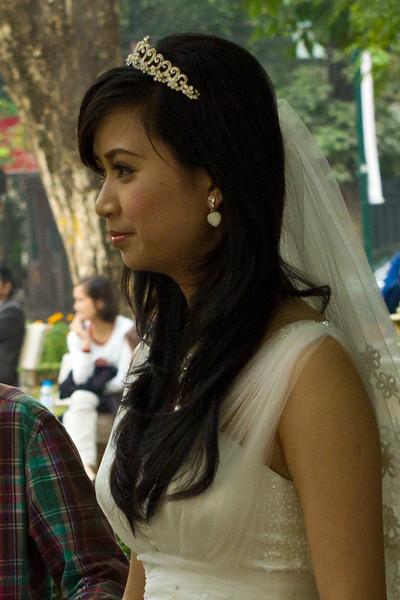 A bride-to-be lakeside near the Tortoise Tower in Hoàn Kiếm Lake, Hanoi, Vietnam.