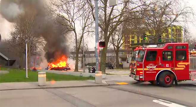 . In this image made from video provided by KOMO-TV, smoke rises from the scene of a news helicopter crash outside the KOMO-TV studios near the space needle in Seattle, Tuesday, March 18, 2014, in Seattle. The station says the copter was apparently coming in for a landing on its rooftop Tuesday morning when it possibly hit the side of the building and went down, hitting several vehicles. (AP Photo/Courtesy KOMO-TV)