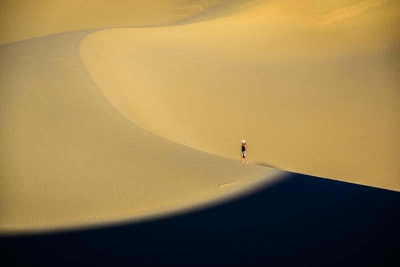 Dune Ridges and shadows converge near a lone hiker.
