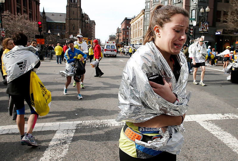 . An unidentified Boston Marathon runner leaves the course crying near Copley Square following an explosion in Boston Monday, April 15, 2013. (AP Photo/Winslow Townson)