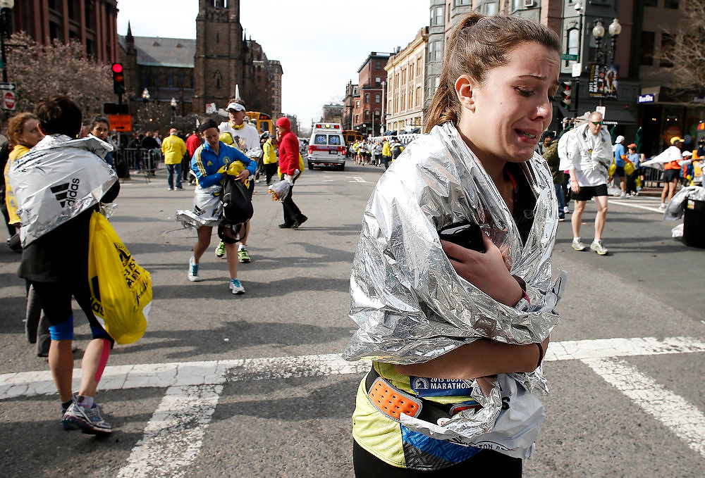Description of . An unidentified Boston Marathon runner leaves the course crying near Copley Square following an explosion in Boston Monday, April 15, 2013. (AP Photo/Winslow Townson)