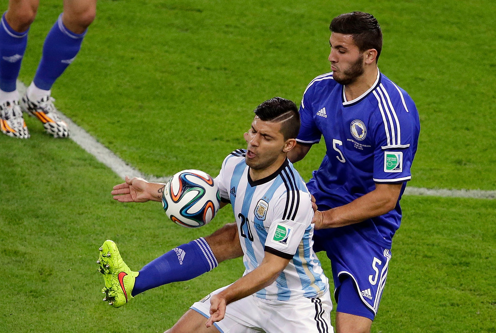 . Argentina\'s Sergio Aguero, left, and Bosnia\'s Sead Kolasinac challenge for the ball during the group F World Cup soccer match between Argentina and Bosnia at the Maracana Stadium in Rio de Janeiro, Brazil, Sunday, June 15, 2014.  (AP Photo/Sergei Grits)