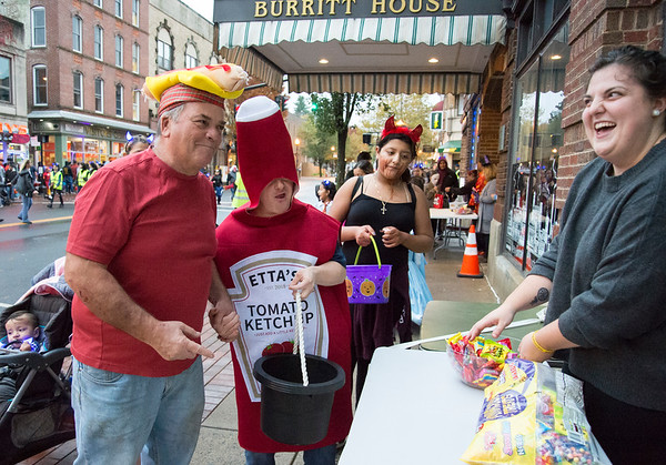 10/31/19 Wesley Bunnell | StaffrrJohn Maynard , guardian for Joe Hamel dressed as a hot dog and ketchup receive candy from New Britain Industrial Museum Director Sophie Huget during the New Britain Down District Halloween Safe Zone 2019.