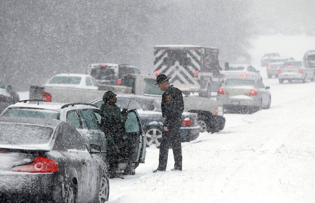 . A Highway Patrol officer checks on the well being of a stranded motorist on Hammond Road during a winter storm Wednesday Feb. 12, 2014, in Raleigh, N.C. (AP Photo/The News & Observer, Travis Long)