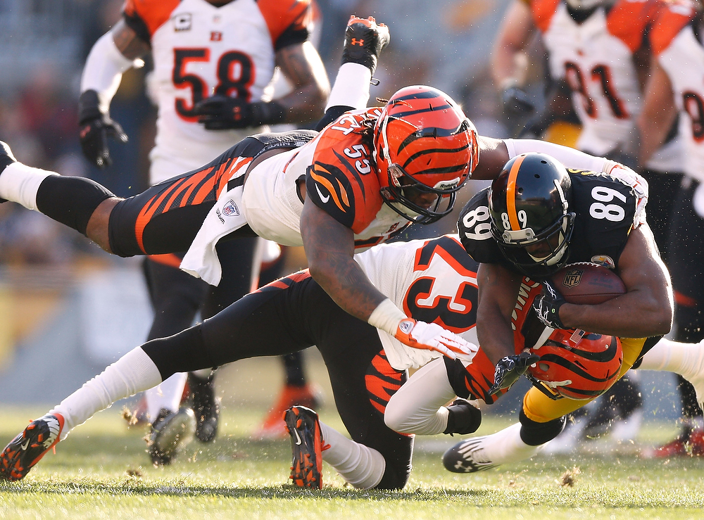 Description of . Jerricho Cotchery #89 of the Pittsburgh Steelers is tackled by Terence Newman #23 and Vontaze Burfict #55 of the Cincinnati Bengals after a second quarter catch at Heinz Field on December 23, 2012 in Pittsburgh, Pennsylvania. (Photo by Gregory Shamus/Getty Images)