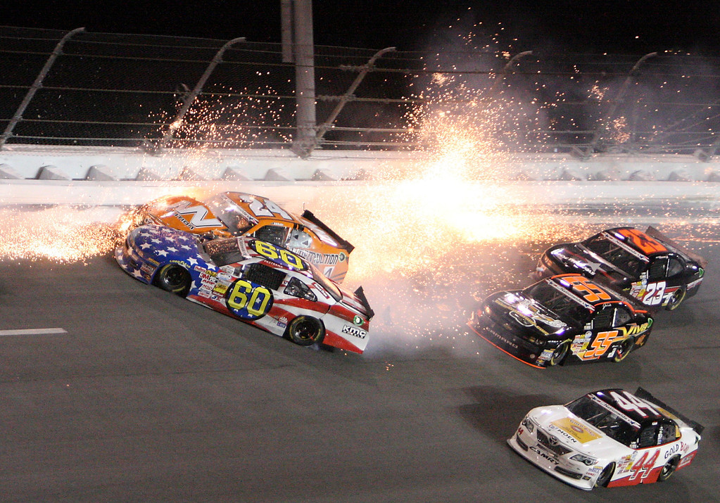 . Travis Pastrana (60) crashes into Jason White (24) in turn 4 of the NASCAR Nationwide auto race at Daytona International Speedway, Friday, July 5, 2013, in Daytona Beach, Fla. (AP Photo/Darryl Graham)