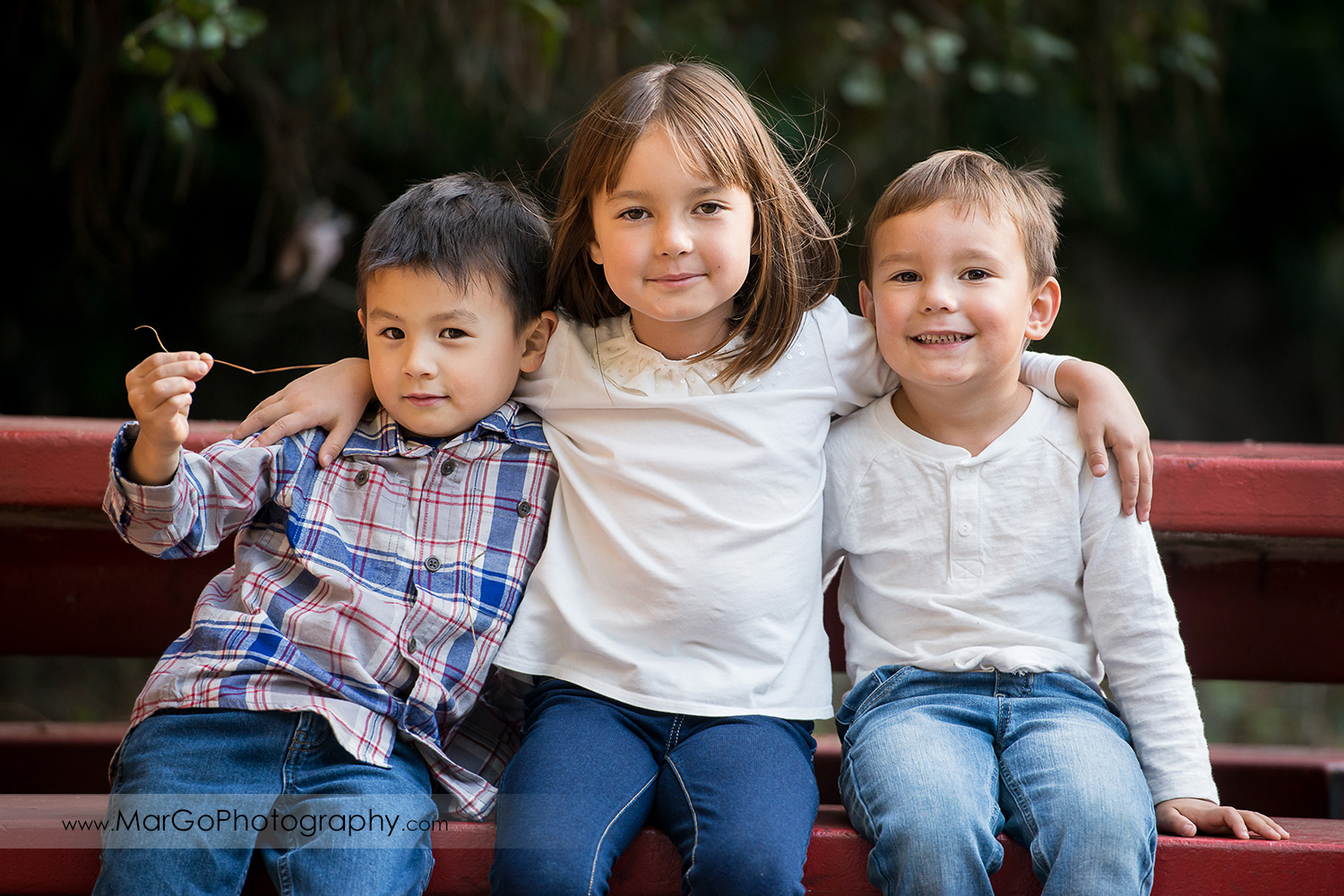 portrait of three little kids in gray and white shirts and jeans sitting on red bench at Carlos Bee Park in Hayward