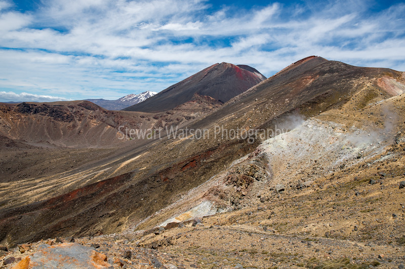 Looking back after passing the red crater then the steep ascent and subsequent descent to the Emerald lakes  (hidden to my left).Mt Ruapehu in the distance.      Amazing colours in the ground/rocks.