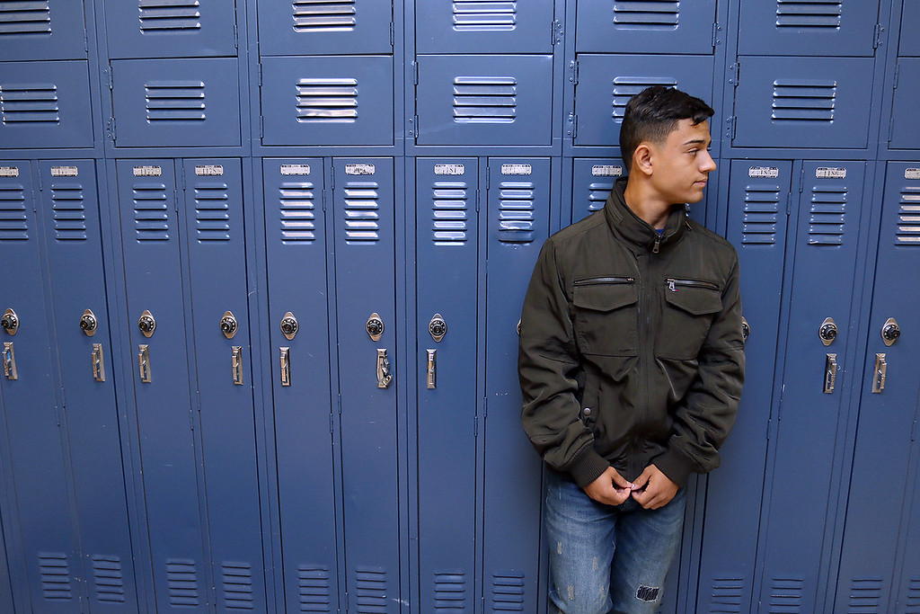 . Adres Crespo, 17, in the hall of Leominster High School on Friday, October 13, 2017. He and his brother moved to Leominster after Hurricane Maria destroyed their town in Puerto Rico. SENTINEL & ENTERPRISE/JOHN LOVE