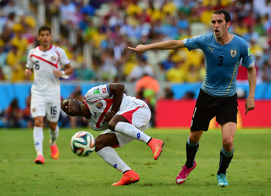 . Uruguay\'s defender Diego Godin (R) gestures as Costa Rica\'s forward Joel Campbell (C) falls during a Group D football match between Uruguay and Costa Rica at the Castelao Stadium in Fortaleza during the 2014 FIFA World Cup on June 14, 2014.  AFP PHOTO / RONALDO SCHEMIDT