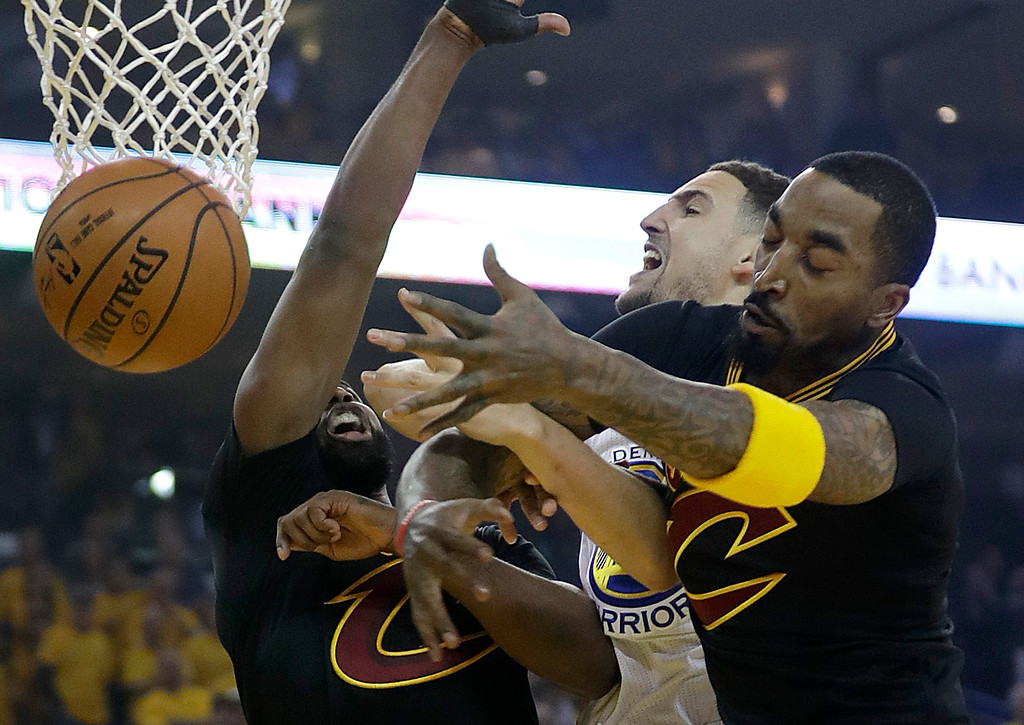 . Golden State Warriors guard Klay Thompson, center, loses the ball while shooting between Cleveland Cavaliers center Tristan Thompson, left, and J.R. Smith during the first half of Game 5 of basketball\'s NBA Finals in Oakland, Calif., Monday, June 12, 2017. (AP Photo/Marcio Jose Sanchez)