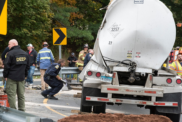10/29/19 Wesley Bunnell | StaffrrA semi trailer carrying hot asphalt overturned on the Mill St exit in Berlin this morning causing asphalt to spill from the top of the tanker mostly onto a grassy divider. State police examine the semi.