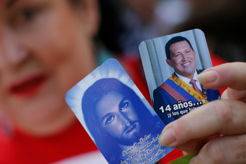 Description of . A supporter of Venezuela's President Hugo Chavez holds pictures of Jesus Christ and Chavez outside the military hospital after his surprise return to Caracas February 18, 2013. Chavez made a surprise return from Cuba on Monday more than two months after surgery for cancer that has jeopardized his 14-year rule of the South American OPEC member. The 58-year-old socialist leader underwent a six-hour operation in Cuba on December 11. He had not been seen or heard in public since then until photos were published of him on Friday. REUTERS/Jorge Silva