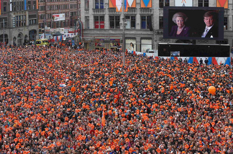. People watch Queen Beatrix\'s abdication ceremony, handing over to her eldest son Willem-Alexander on a giant screen in Amsterdam\'s Dam Square April 30, 2013. Queen Beatrix of the Netherlands abdicated on Tuesday, handing over to her eldest son, Willem-Alexander, who became the first King of the Netherlands in over 120 years. REUTERS/Kevin Coombs