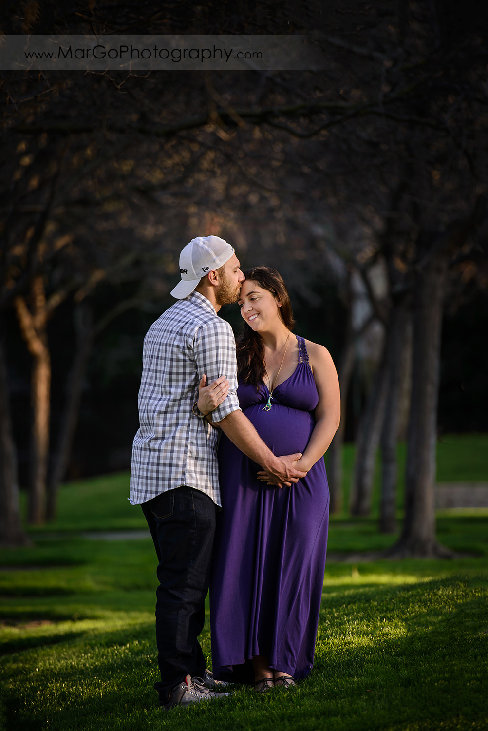 full body portrait of man in checkered shirt and pregnant woman in long violet dress during maternity session at Lick Mill Park in Santa Clara