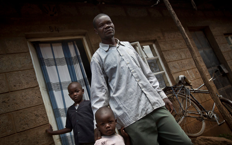 . Former Westgate Mall security guard David Odhiambo, 36, stands with his daughter Benta, 4, center, and son Isaac, 7, left, outside his one-room house where he lives with his wife and five children in the Kawangware slum of Nairobi, Kenya on Aug. 27, 2014. Odhiambo was one of the blue-uniformed security guards tasked with protecting Nairobi\'s Westgate Mall one year ago when four heavily armed terrorists attacked, earning him two bullets in the head. (AP Photo/Ben Curtis)