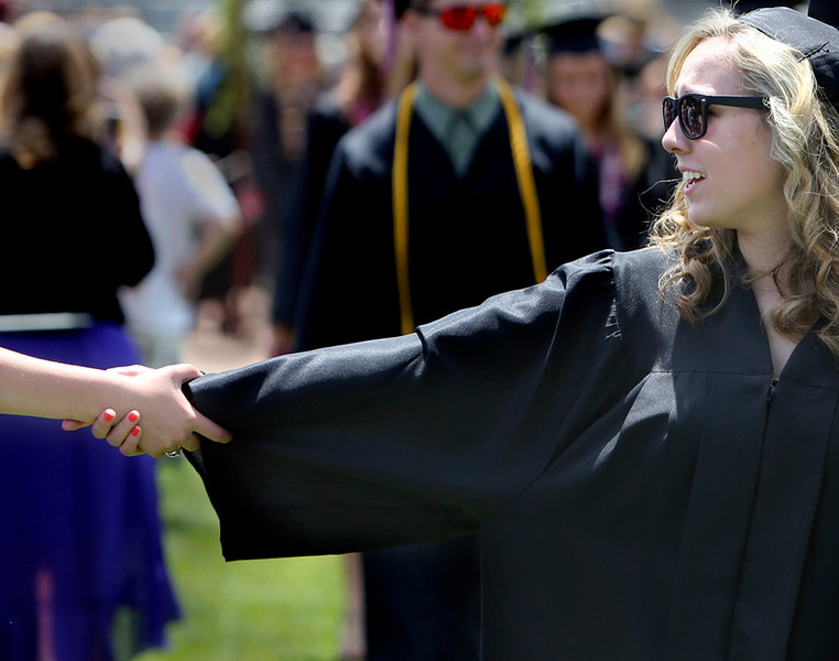 . SLV grads reach out to friends and family at they walk towards the stage at the San Lorenzo Valley High baseball field on Friday afternoon. (Kevin Johnson/Sentinel)