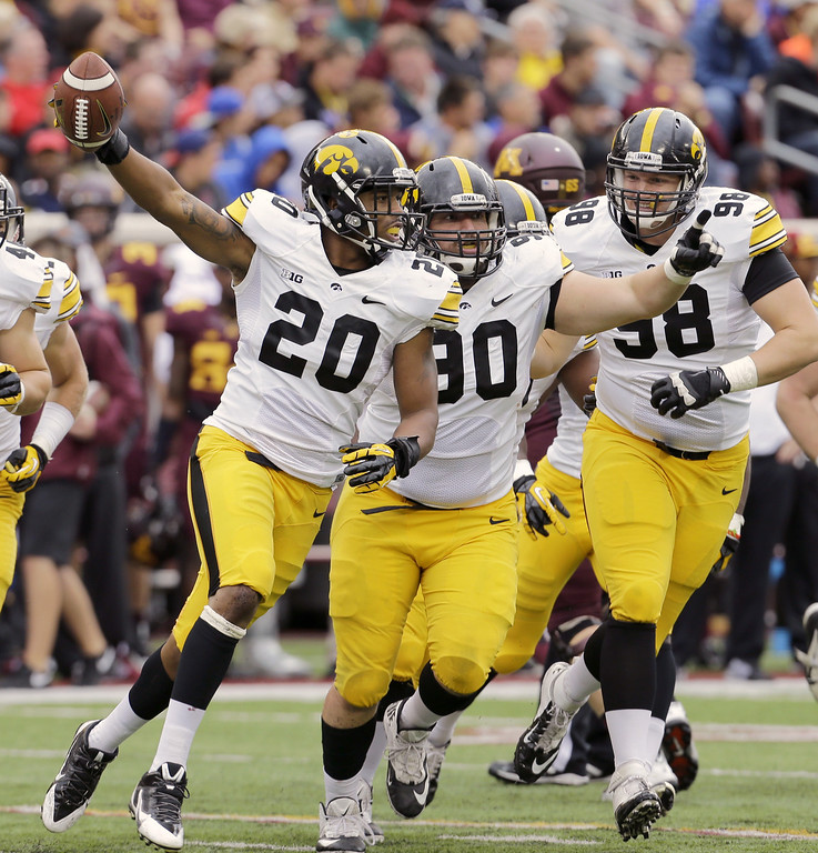 . Iowa  linebacker Christian Kirksey (20) and defensive lineman Louis Trinca-Pasat, center, and defensive lineman Mike Hardy, right, celebrate after Kirksey intercepted a pass from Minnesota quarterback Philip Nelson (9) during the second quarter of an NCAA college football game on Saturday, Sept. 28, 2013, in Minneapolis. (AP Photo/Ann Heisenfelt)