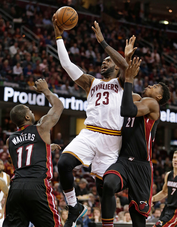 . Cleveland Cavaliers\' LeBron James (23) drives to the basket against Miami Heat\'s Dion Waiters (11) and Hassan Whiteside (21) in the first half of an NBA basketball game, Monday, March 6, 2017, in Cleveland. (AP Photo/Tony Dejak)