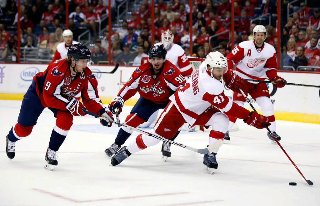 . Detroit Red Wings right wing Luke Glendening (41) works to control the puck as he is pursued by Washington Capitals center Nicklas Backstrom (19), from Sweden, and left wing Marcus Johansson (90), from Sweden, in the first period of an NHL hockey game, Wednesday, Oct. 29, 2014, in Washington. (AP Photo/Alex Brandon)