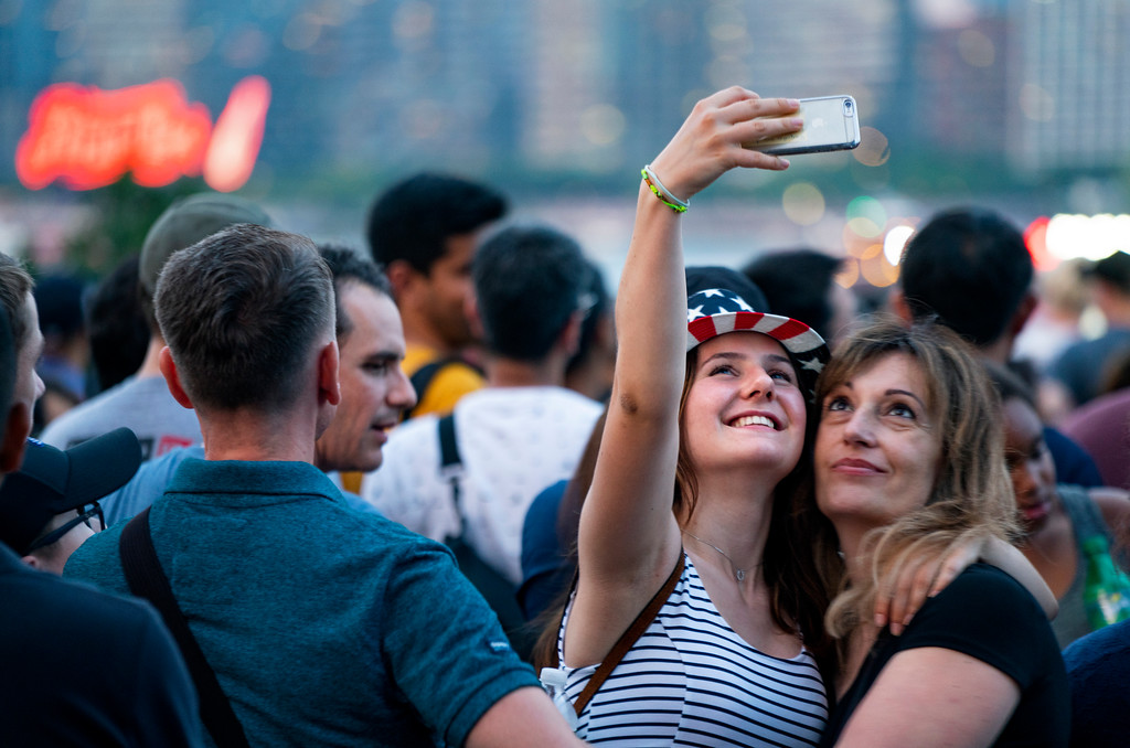 . Visitors who said they are from Switzerland take a photo of one another as they wait with other spectators on the east side of Manhattan borough before a fireworks display, part of Independence Day festivities Wednesday, July 4, 2018, in New York. (AP Photo/Craig Ruttle)