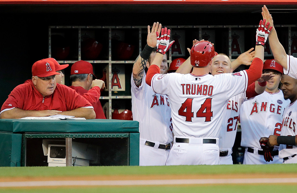 . Los Angeles Angels\' Mark Trumbo( 44) celebrates his home run with teammates as manager Mike Scioscia, left, watches during the second inning of a baseball game against the Seattle Mariners in Anaheim, Calif., Tuesday, June 18, 2013. (AP Photo/Jae C. Hong)