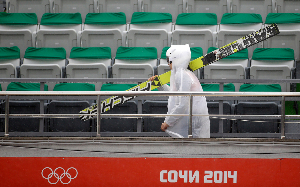 . Japan\'s Hideaki Nagai carries his ski over the empty stands as rain pours down during the Nordic combined individual Gundersen large hill competition at the 2014 Winter Olympics, Tuesday, Feb. 18, 2014, in Krasnaya Polyana, Russia. (AP Photo/Gregorio Borgia)