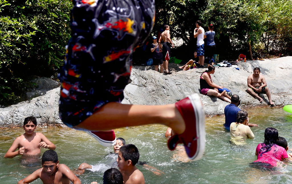 . People play in the San Gabriel River along the East Fork  in the Angeles National Forest Saturday, July 20, 2013. The Urban Conservation Corps educates people visiting the East Fork of the San Gabriel River in the Angeles National Forest. Although the Urban Conservation Corps says their river trash count studies show less trash the area is still littered with garbage. (SGVN/Staff Photo by Sarah Reingewirtz)
