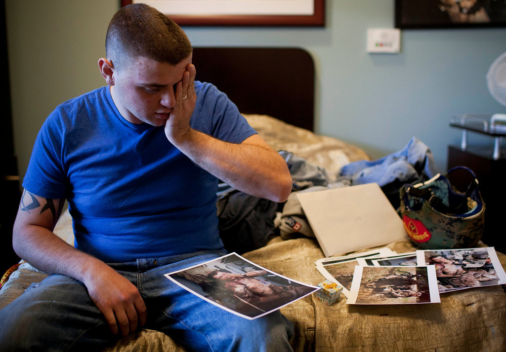 . In this Tuesday, Dec. 13, 2011 file photo made by Associated Press photographer Anja Niedringhaus, injured United States Marine Cpl. Burness Britt reacts after seeing pictures of his evacuation laid out on his bed in the Hunter Holmes Medical Center in Richmond, Va.  (AP Photo/Anja Niedringhaus, File)