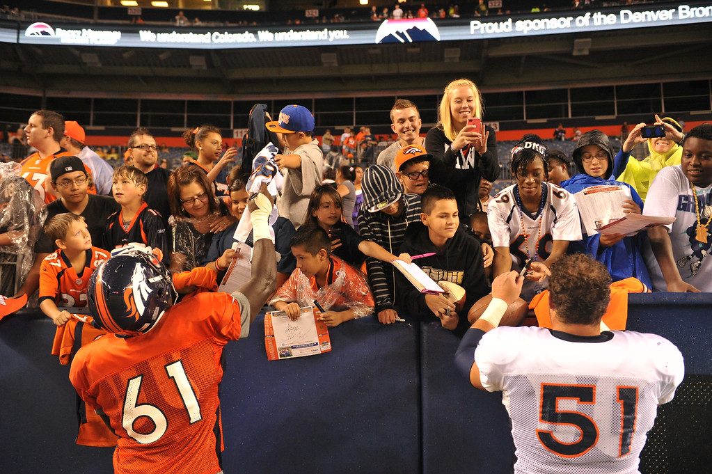 . DENVER, CO. - August 03: Lanston Tanyl (61) and Steve Vallos (51) of Denver Broncos sign autographs for the fans after the summer scrimmage at Sports Authority Field at Mile High. Denver, Colorado. August 03, 2013. (Photo By Hyoung Chang/The Denver Post)