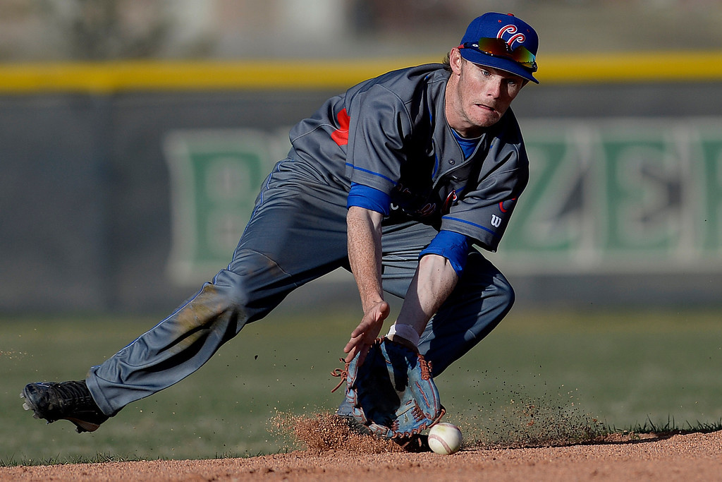 . Aurora, CO - APRIL 08: Jack Hallmark (11) of the Cherry Creek Bruins fields a ball hit by Joseph Sanchez (18) of the Overland Trailblazers before overthrowing first base during the seventh inning. Overland hosted Cherry Creek on Tuesday, April 8, 2014. (Photo by AAron Ontiveroz/The Denver Post)