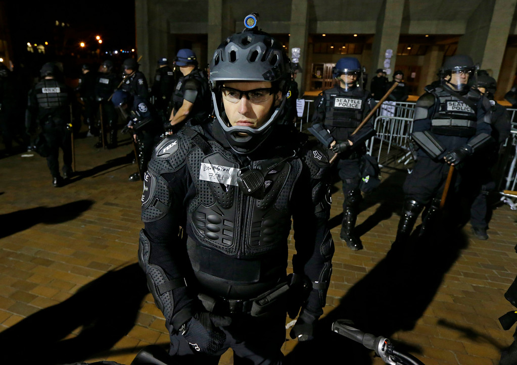 . Seattle Police officers dressed in protective gear stand outside Kane Hall on the University of Washington campus during a protest while far-right commentator Milo Yiannopoulos was giving a speech, Friday, Jan. 20, 2017, in Seattle. (AP Photo/Ted S. Warren)