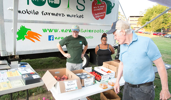 08/05/19 Wesley Bunnell | Staff Nic Tedesco, L, and Jasiry Valentin assist customer Fred Hurlbert at the New Britain Roots mobile farmers market truck on Monday evening during a concert at Walnut Hill Park.