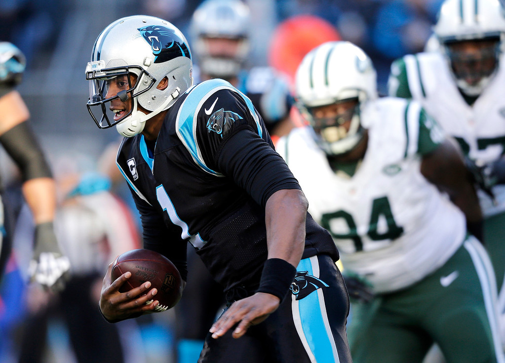 . Carolina Panthers quarterback Cam Newton (1) scrambles for a short gain as New York Jets\' Damon Harrison (94) pursues during the first half of an NFL football game in Charlotte, N.C., Sunday, Dec. 15, 2013. (AP Photo/Chuck Burton)