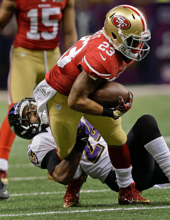 . Baltimore Ravens cornerback Corey Graham (24) pulls down San Francisco 49ers running back LaMichael James (23) in the second quarter of the NFL Super Bowl XLVII football game, Sunday, Feb. 3, 2013, in New Orleans. (AP Photo/Dave Martin)