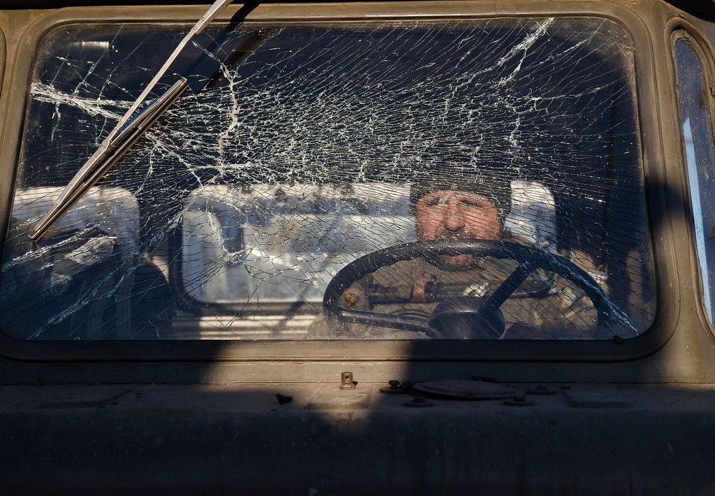 . A Ukrainian serviceman sits inside a broken down vehicle outside Artemivsk, Ukraine, while pulling out of Debaltseve, Wednesday, Feb. 18, 2015. After weeks of relentless fighting, the embattled Ukrainian rail hub of Debaltseve fell Wednesday to Russia-backed separatists, who hoisted a flag in triumph over the town. The Ukrainian president confirmed that he had ordered troops to pull out and the rebels reported taking hundreds of soldiers captive. (AP Photo/Vadim Ghirda)