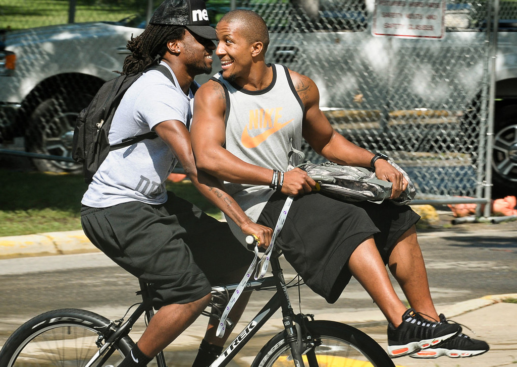 . Vikings cornerback Josh Robinson, right, takes a joyride on the bike of strong safety Mistral Raymond as they head to a team meeting after checking in at training camp.  (Pioneer Press: Ben Garvin)