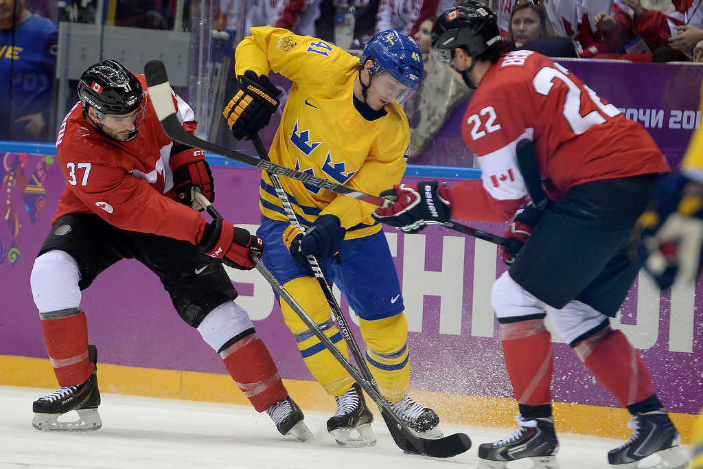 . Gustav Nyquist (41) of Sweden is defended tightly by Patrice Bergeron (37) of Canada and Jamie Benn (22) during the first period of the men\'s ice hockey gold medal game. Sochi 2014 Winter Olympics on Sunday, February 23, 2014 at Bolshoy Ice Arena. (Photo by AAron Ontiveroz/ The Denver Post)