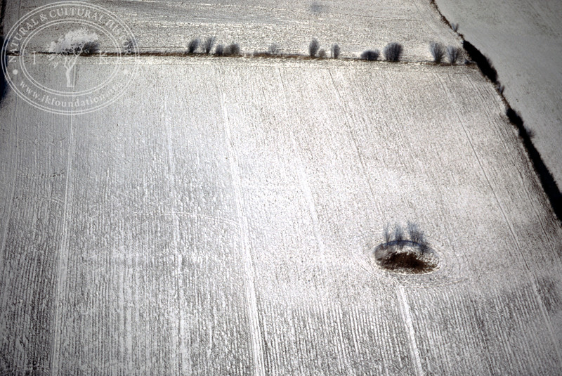 Farmland west of Ravlunda church - with plantations, buildings and prehistoric remains (20 February, 1988). | LH.0207