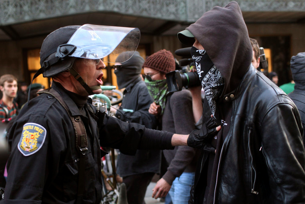 . A Seattle Police Department officer pushes a demonstrator during May Day demonstrations in Seattle, Washington May 1, 2013. Protesters clashed with police in Seattle on Wednesday as a May Day rally that began peacefully turned violent after dark, with demonstrators hurling objects at officers who responded by firing flash-bang grenades and pepper spray.     REUTERS/Matt Mills McKnight